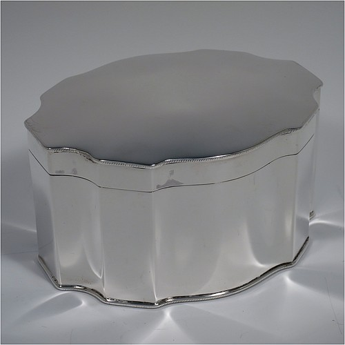 An Antique Sterling Silver Chippendale style table box, having a shaped oval and straight-sided body with a hinged and slightly domed lid, an applied rope-twist border, and sitting on a flat base. Made by Ellis Jacob Greenberg of Birmingham in 1917. The dimensions of this fine hand-made antique silver box are length 14 cms (5.5 inches), width 11 cms (4.3 inches), height 8 cms (3 inches), and it weighs approx. 425g (13.7 troy ounces).