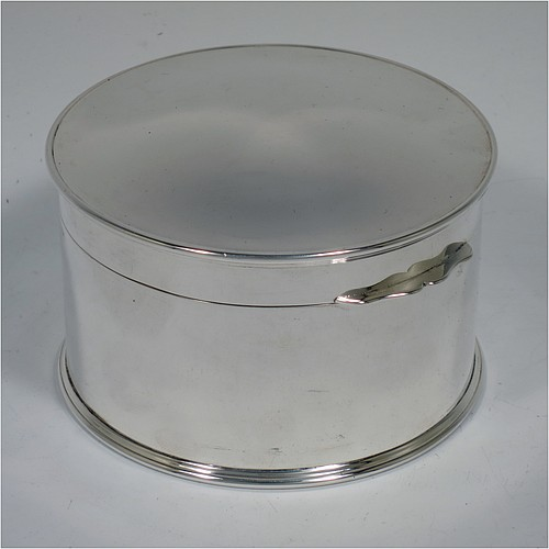 A Sterling Silver table box, having a round and straight-sided body with a hinged and slightly domed lid, with applied reed borders and thumb-piece, and sitting on a flat base. Made by Goldsmiths and Silversmiths of London in 1929. The dimensions of this fine hand-made silver box are diameter 10 cms (4 inches), height 6 cms (2.3 inches), and it weighs approx. 364g (11.7 troy ounces).