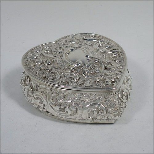 A very pretty Antique Victorian Sterling Silver heart-shaped table box, having a  gold-gilt interior, all hand-chased with flowers and scroll-work, and sitting on a flat base. Made by Henry Matthews of Birmingham in 1908. The dimensions of this fine hand-made antique silver box are length 10 cms (4 inches), width 9 cms (3.5 inches), height 4 cms (1.5 inches), and it weighs approx. 96g (3 troy ounces).