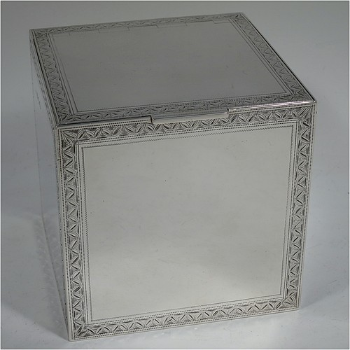 A very fine, unusual, and handsome heavy Sterling Silver table box, having a cube-shaped body, with an invisibly hinged lid, and hand-engraved with bright-cut floral leaf-work borders, and sitting on a flat base. Beautifully and skilfully hand-made made by Robert Comyns of London in 1938. The dimensions of this fine hand-made silver box are 11.5 cms (4.5 inches) cubed, and it weighs approx. 890g (29 troy ounces).