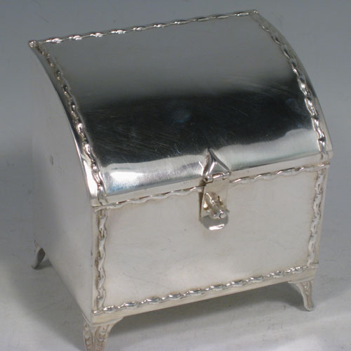 Antique Victorian sterling silver table box, in a casket style, having a plain rectangular body, with hinged and curved lid having a clasp and lock on the front of the body, together with applied floral bands, and sitting on four foliate feet. Made in Birmingham in 1904. Height 10 cms (4 inches), length 9.5 cms (3.75 inches), depth 7 cms (2.75 inches). Weight 240g (7.7 troy ounces).