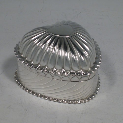 Antique Victorian sterling silver box, having a heart-shaped body, hinged lid with vacant cartouche, and hand-chased fluted decoration. Made by Harold and Ashwin of Birmingham in 1890. Length 7.5 cms (3 inches), height 5 cms (2 inches). Weight approx. 75g (2.4 troy ounces).