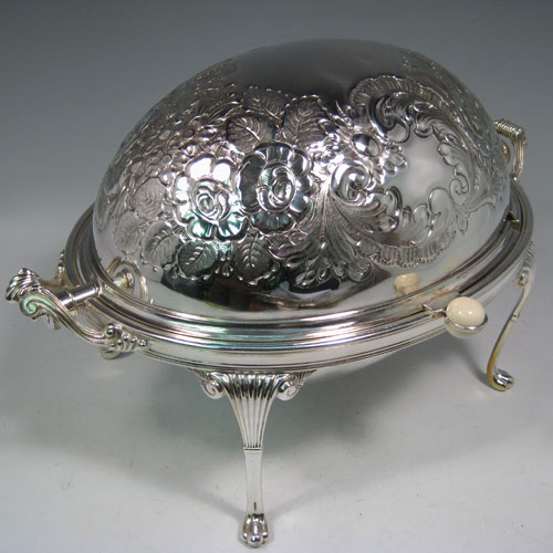 Antique Victorian silver-plated breakfast dish with revolving lid, original liners, and having hand-chased florally decorated body, sitting on four cast fluted feet. Made by Harrison Brothers and Howson of Sheffield in ca. 1870. Height 22 cms (8.5 inches), length 36 cms (14 inches), width 23 cms (9 inches).