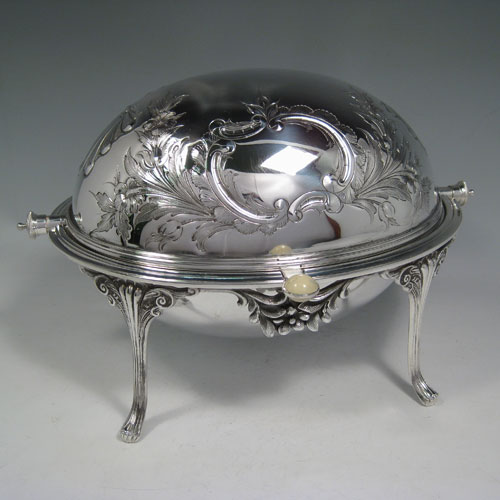 Antique Victorian silver plated revolving breakfast dish with hand-chased floral decoration, cast foliate feet, and original liners. Made by James Round of Sheffield in ca. 1880. Height 21.5 cms (8.5 inches), length 33 cms (13 inches), width 23 cms (9 inches).