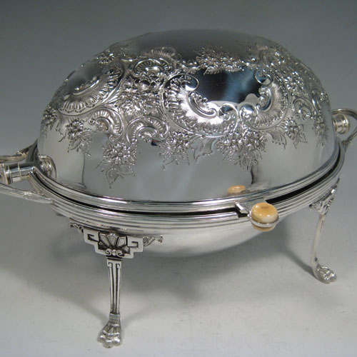 Antique Victorian silver-plated breakfast dish with revolving lid, original liners, and having hand-chased florally decorated body, sitting on four cast lions-paw feet. Made by Harrison Brothers and Howson of Sheffield in ca. 1880. Height 21 cms (8.25 inches), length 36 cms (14 inches), width 23 cms (9 inches).