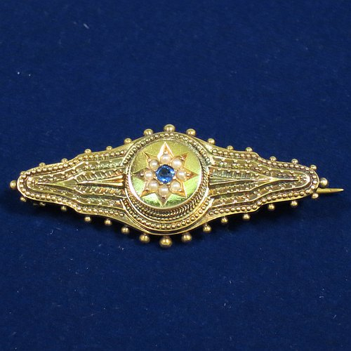 An Antique Victorian Etruscan style 15ct carat gold brooch, having an elongated and shaped oval body, with applied bead decoration, and a stepped round centre with star decoration having a sapphire and small pearls, and the back having a pin and a security ring but no chain. Made in ca. 1880. The dimensions of this fine antique gold brooch are length 4.5 cms (1.75 inches), width 2 cms (0.75 inch), and it weighs approx. 3.5g.