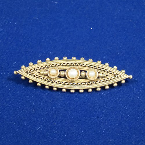 An Antique Victorian Etruscan style 15ct carat gold brooch, having an elongated oval body, with applied bead decoration, and a centre with three old graduated pearls, and the back having a security pin. Made in ca. 1880. The dimensions of this fine antique gold brooch are length 5 cms (2 inches), width 2 cms (0.75 inch), and it weighs approx. 4.8g.