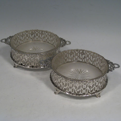 Sterling silver pair of butter dishes, having hand-pierced bodies, cast ribbon and laurel-leaf handles, frosted hand-cut crystal interiors, and sitting on four cast floral feet. Made by Edward Barnsley of Birmingham in 1912. Diameter 11 cms (4.25 inches), height 4.5 cms (1.75 inches). Total weight approx. 150g (4.8 troy ounces).