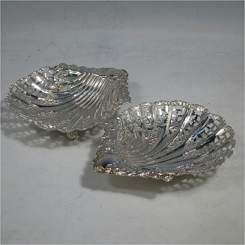 An Antique Victorian Sterling Silver pair of butter shells, having hand-chased and hand-pierced scalloped bodies with floral decoration, and both sitting on three ball feet. All made by Henry Atkins of Sheffield in 1896. The dimensions of these fine hand-made antique silver butter dishes are length 10 cms (4 inches), height 2 cms (0.75 inch), and they have a total weight of 69g (2.2 troy ounces).