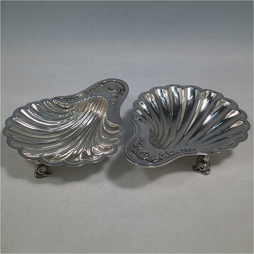 An Antique Sterling Silver pair of butter shells, having a traditional scallop shape, with hand-chased neoclassical style decoration on the handles, and sitting on cast dolphin style feet. Made by Elkington & Co., of Birmingham in 1913. The dimensions of this fine hand-made pair of antique butter shells are length 15 cms (6 inches), width 12 cms (4.75 inches), and with a total weight of approx. 310g (10 troy ounces).