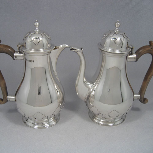 Sterling silver pair of cafe-au-lait pots made by Hamilton & Co., of London in 1919. With cut-card work decoration. Height 23 cms. Weight approx. 49 troy ounces.