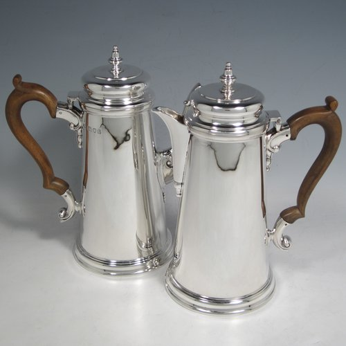 Sterling silver pair of cafe-au-lait pots, in a George I style, having very plain round bodies with tapering sides, brown wooden scroll side-handles, cushioned hinged lids with silver finials, and sitting on flat bases. Made by C. J. Vander of London in 1936. The dimensions of this fine pair of silver cafe-au-lait pots are height 20 cms (8 inches), length of coffee pot 19 cms (7.5 inches), and they weigh approx 930g (30 troy ounces).