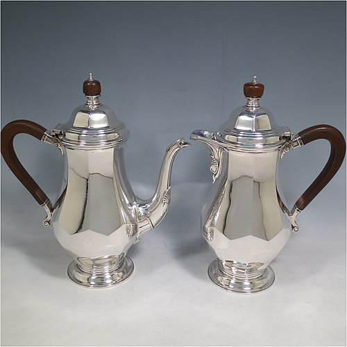 A Sterling Silver heavy pair of Art Deco cafe-au-lait pots, having plain panelled and faceted bodies, with brown wooden scroll handles and finials, hinged and panelled domed lids with finials, and sitting on pedestal feet. Made by the Adie Brothers of Sheffield in 1927. The dimensions of this fine hand-made pair of Art Deco silver cafe-au-lait pots are height 24 cms (9.5 inches), length of coffee pot 21 cms (8.25 inches), and they weigh approx. 1,395g (45 troy ounces).