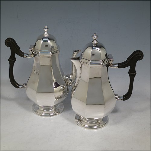 An Antique Sterling Silver pair of cafe-au-lait pots, having plain panelled and bellied bodies, with black wooden scroll handles, hinged and panelled domed lids with cast finials, and sitting on pedestal feet. Made by the Goldsmiths & Silversmiths of London in 1913. The dimensions of this fine hand-made pair of antique sterling silver cafe-au-lait pots are height 17 cms (6.75 inches), length of coffee pot 14.5 cms (5.75 inches), and they weigh approx. 495g (16 troy ounces).