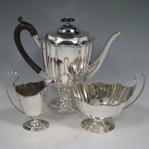 Sterling silver three-piece coffee set, having plain tapering bodies with shaped shoulders, insulated wooden handle, hinged lid with wooden finial, loop handles, and all sitting on pedestal feet. Made by William Hutton of Sheffield in 1911. The dimensions of this fine silver coffee service are height of coffee pot 23 cms (9 inches), length of coffee pot 24 cms (9.5 inches), and the total weight is approx. 992g (32 troy ounces).