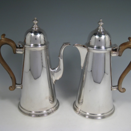 Silver-plated pair of cafe-au-lait serving pots in the George I style with domed hinged lids, straight sided, and wooden handles. Made by Aspreys of London in ca. 1950. Height 25.5 cms (10 inches), length of coffee pot 19 cms (7.5 inches).