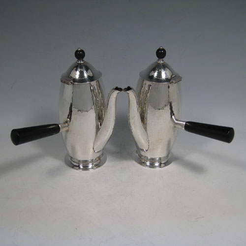 Antique Sterling silver pair of Arts and Crafts style cafe-au-lait pots, having round tapering bodies with hand-hammered decoration, hinged lids with wooden finials, and wooden side-handles. Made by Henry Wilkinson of Sheffield in 1911. Height 10 cms (7 inches), length 15 cms (6 inches). Total weight approx. 550g (17.8 troy ounces).