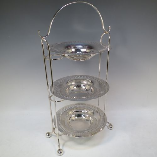 A pretty Antique Edwardian Silver Plated three-tier cake stand, having a suite of three removable round plates with pierced borders and fairly deep bowls, sitting within a very pretty wire-work frame with scroll-work handle and four ball feet. Made in ca. 1900. The dimensions of this fine hand-made antique silver-plated cake stand are height 49 cms (19.25 inches), width across feet at base 26 cms (10.25 inches), and diameter of plates are 21 cms (8.25 inches).
