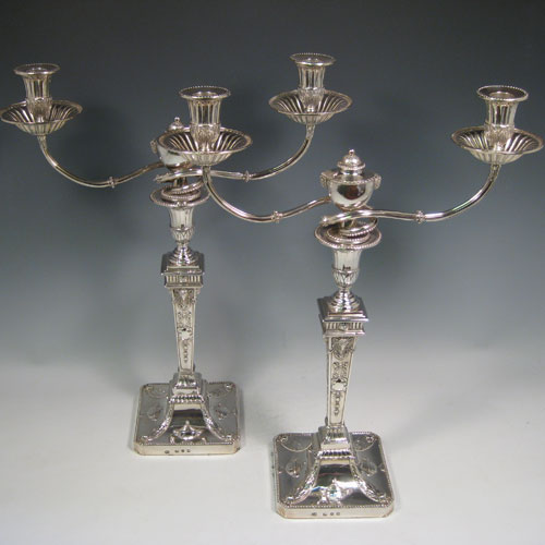 Antique Georgian sterling silver rare and fine pair of two-light candelabra made by John Steward of London in 1775. All hand-chased with Neoclassical style decoration including swags, rams heads, and tureens. Together with bead edges and fluted decoration on the nozzles. Height 45 cms (17.75 inches), width 35 cms (13.75 inches).