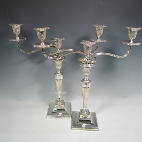 An Antique Georgian and 20th Century sterling silver pair of three-light candelabra with removable reed-work arms, hand-chased fluted decoration, square cross-section columns and bases, and applied Anthemion leaf borders. Please note that the candelabra bases are Georgian and made by Tudor & Leader of Sheffield in 1782, and the matching candelabra branches are made in London in 1956. The dimensions of this fine pair of hand-made silver candelabra are height 44 cms (17.25 inches), and spread across branches 43 cms (17 inches).