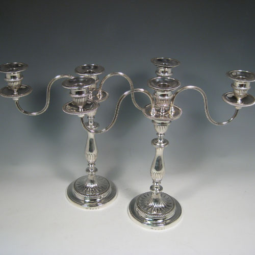 Antique Georgian / Victorian sterling silver pair of three-light candelabra with removable arms, fluted decoration, and straight gadroon borders. Please note that the candelabra bases are made by Alexander Goodman & Co., of Sheffield in 1800, and the matching candelabra branches are made by the Barker Brothers of London in 1878. Height 34 cms (13.5 inches), spread across branches 41 cms (16 inches).