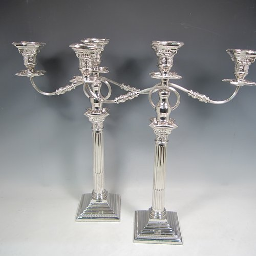 A Sterling silver pair of candelabra in the Corinthian style, having removable arms with three lights, fluted columns with stepped square bases, double swirl reeded arms, acanthus leaf capitals, removable nozzles with drip pans, and bead-edged borders. Made in London in 1933. The dimensions of this fine hand-made silver pair of candelabra are height 49 cms (19.25 inches), and spread across arms 40 cms (15.75 inches).