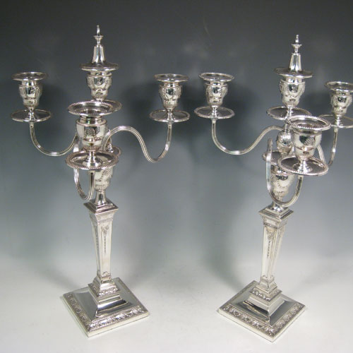 Antique Victorian sterling silver and silver-plated pair of four-light candelabra, having square bases and collumns with neoclassical style chased work, removable arms with drip pans, nozzles, and extinguishers, all with beaded borders. Please note that the bases are sterling silver and the arms are silver-plate. Made by J.K. Bembridge of Sheffield in 1884. Height 47 cms (18.5 inches), spread across arms 27 cms (10.5 inches).