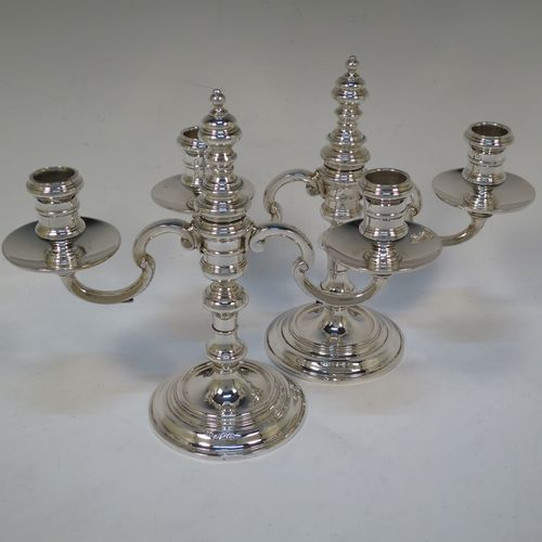 A handsome Sterling silver pair of George I style three-light candelabra, having plain round baluster bodies, fixed arms with drip pans, and central finial that can be pulled out to uncover the third candle holder. Made by Robert Comyns of London in 1937. The dimensions of this fine hand-made pair of silver candelabra are height 20 cms (8 inches), spread across arms 23 cms (9 inches), and with a total weight of approx. 809g (26 troy ounces). Please note that these candelabra are not filled.