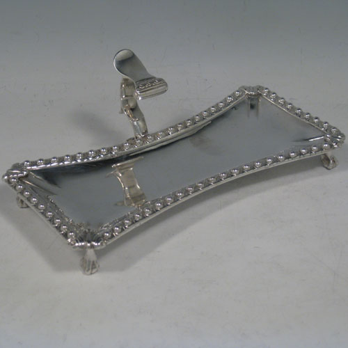Antique Georgian sterling silver candle scissor snuffer stand, having a plain shaped rectangular body, with an applied cast bead-edged border, a cast scroll handle with thumb-piece, and sitting on four cast lions claw and ball feet. Made by Ebenezer Coker of London in 1770. The dimensions of this fine hand-made silver snuffer stand are length 19 cms (7.5 inches), height including handle 6.5 cms (2.5 inches), width 9 cms (3.5 inches), and it weighs approx. 234g (7.5 troy ounces).
