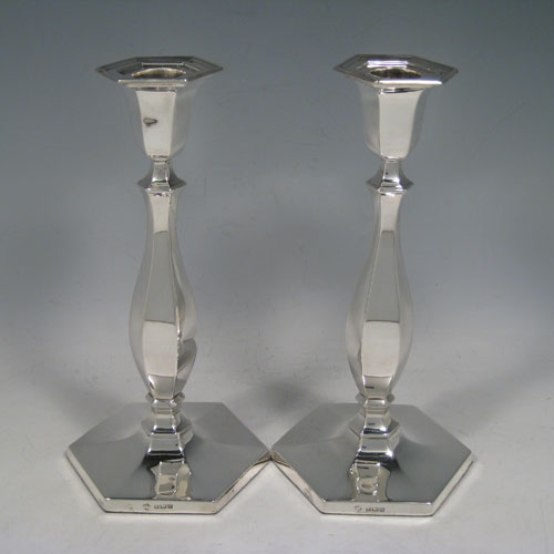 Sterling silver pair of Art Deco candlesticks, having plain hexagonal bodies, with removable nozzles, and sitting on pedestal bases. Made by William Hutton and Sons of Birmingham in 1930. The dimensions of this fine pair of hand-made silver candlesticks are height 21 cms (8.25 inches), and width of bases 9.5 cms (3.75 inches).