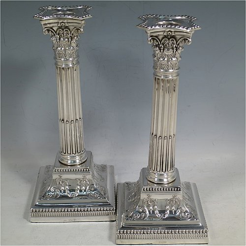An Antique Sterling Silver pair of candlesticks, in a Neoclassical Corinthian style with square bases and round straight-sided fluted columns, having applied beaded borders, with hand-chased swags and scrolls, and removable nozzles. Made by James Dixon of Sheffield in 1912. The dimensions of this fine pair of hand-made antique silver candlesticks are height 22 cms (8.75 inches), and the bases are 9.5 cms (3.75 inches) square.