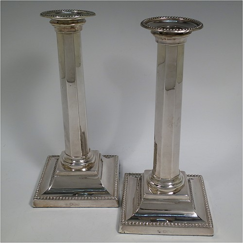 An Antique Victorian Sterling Silver pair of very pretty table candlesticks with bead-edged borders, having square bases with straight hexagonal panelled columns, with plain round capitals and removable nozzles. Made by Martin Hall and Co., of Sheffield in 1897. The dimensions of this fine hand-made pair of antique silver candlesticks are height 23 cms (9 inches), and 11 cms (4.3 inches) square at the base.