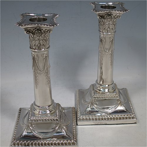 An Antique Edwardian Sterling Silver pair of candlesticks, in a Neoclassical Corinthian style with square bases and round straight-sided columns, having applied gadroon borders, hand-chased bows with swag decoration, and removable nozzles. Made by Henry Wilkinson of Sheffield in 1902. The dimensions of this fine pair of hand-made antique silver candlesticks are height 19 cms (7.5 inches), and the bases are 10 cms (4 inches) square.