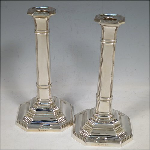 A Sterling Silver pair of Art Deco style candlesticks, having panelled bodies, with hand-chased reeded borders and fluted corners, and removable nozzles. Made by Ellis Jacob Greenberg of Birmingham in 1920. The dimensions of these fine hand-made silver table candlesticks are height 18.5 cms (7.3 inches), and width at base 9.5 cms (3.75 inches).