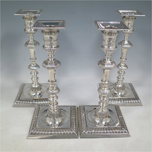 An Antique Edwardian Sterling Silver handsome set of four candlesticks in a George I style, having round baluster bodies, with removable square nozzles, and sitting on square bases, all with hand-chased fluted decoration and applied gadroon borders. Made by Thomas Bradbury of London in 1904. The dimensions of these fine hand-made antique silver table candlesticks are height 23.5 cms (9.25 inches), and the bases are 11 cms (4.3 inches) square.