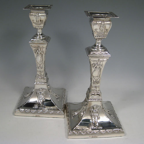 Antique Edwardian sterling silver pair of square-based candlesticks decorated in a neoclassical style with swags and greco-roman figures. Made by William Comyns of London in 1904. Height 24 cms (9.5 inches), width at base 11.5 cms (4.5 inches).