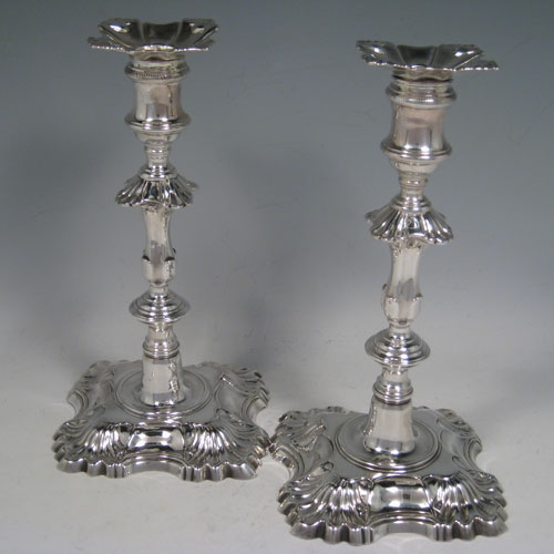 Antique Georgian cast sterling silver pair of candlesticks with removable bobeches, baluster style bodies, and four-shell bases. Made by John Priest of London in 1751/2. Height 21.5 cms (8.5 inches). Total weight approx. 960g (31 troy ounces).