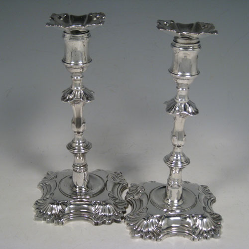 Antique Georgian George II cast sterling silver pair of candlesticks, having baluster bodies, four-shell bases, and removable nozzles. Made by John Cafe of London in 1754. Height 20.5 cms (8 inches). Total weight 889g (28.7 troy ounces).