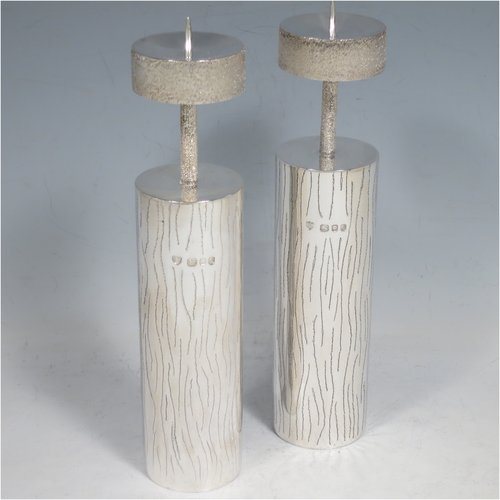 A Sterling Silver pair of candlesticks in a Modernistic style, having cylindrical bodies with hand-chased tree-bark decoration, together with capitals and candle spikes with an unusual stippled finish. Made by Michael Bensted of London in 1975. The dimensions of these fine hand-made pair of silver table candlesticks are height 19 cms (7.5 inches), diameter 4 cms (1.5 inches), and they weigh a total of approx. 437g (14.1 troy ounces). Please note that these candlesticks are not filled.