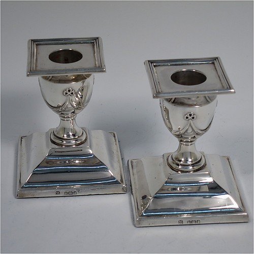 An Antique Victorian Sterling Silver very pretty pair of small candlesticks, having neoclassical style decoration with rectangular bases, with hand-chased bows and swags, and removable nozzles with applied reeded borders. Made by William Angus Fraser of Sheffield in 1894. The dimensions of these fine hand-made antique silver candlesticks are height 8 cms (3.25 inches), and the bases are 7 cms (2.75 inches) square.