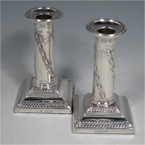 An Antique Edwardian Sterling silver pair of candlesticks, in a Neoclassical style with bead- edged borders, having straight round columns with hand-chased oak leaves and acorns, sitting on stepped bases, and with removable nozzles. Made by Thomas Bradbury of London in 1896. The dimensions of this fine pair of hand-made silver candlesticks are height 13 cms (5.25 inches), and the bases are 8 cms (3 inches) square.