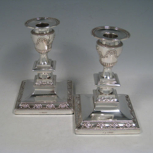 Antique Victorian sterling silver pair of candlesticks, having square bases with baluster bodies, hand-chased neoclassical style decoration, bead-edged borders, and removable nozzles. Made by J.K. Bembridge of Sheffield in 1879. The dimensions of these fine hand-made silver candlesticks are height 16 cms (6.3 inches), and the bases are 11 cms (4.3 inches) square.