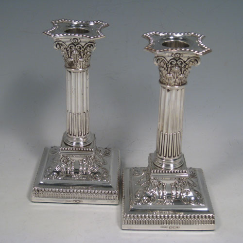 Antique Victorian sterling silver pair of Corinthian style candlesticks, having beeded borders, acanthus-leaf capitals, fluted columns, removable nozzles, and hand-chased square bases with floral decoration. Made by James Dixon and Sons of Sheffield in 1900. Height 17 cms (6.75 inches), bases are 9 cms (3.5 inches) square.