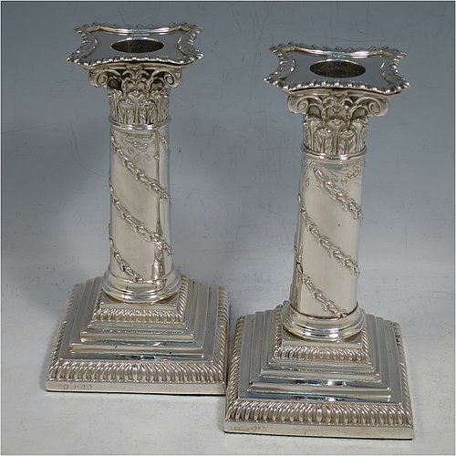 An Antique Victorian Sterling Silver pair of candlesticks, in the Corinthian style with gadroon-edged borders, removable nozzles, having columns with hand-chased garlands of flowers, and square stepped bases. Made by J. K. Bembridge of Sheffield in 1891. The dimensions of this fine pair of hand-made antique silver candlesticks are height 16 cms (6.25 inches), and the bases are 8.5 cms (3.3 inches) square.