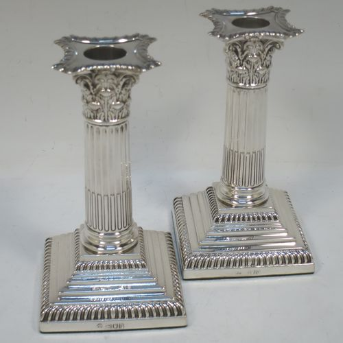 A very pretty pair of Antique Victorian Sterling Silver of Corinthian style candlesticks, having traditional gadroon borders, acanthus-leaf capitals, fluted columns, removable nozzles, and square stepped bases. Made by William Hutton of London in 1901. The dimensions of this fine hand-made pair of antique silver candlesticks are height 16 cms (6.25 inches), and the bases are 8.5 cms (3.3 inches) square.
