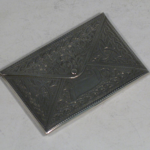 Antique Edwardian sterling silver card case, having a rectangular body in the shape of an envelope, with hand-engraved floral work, a hinged lid / tongue with clasp. Made in Birmingham in 1905. Length 9.5 cms (3.75 inches), width 6.5 cms (2.5 inches). Weight approx. 63g (2 troy ounces).