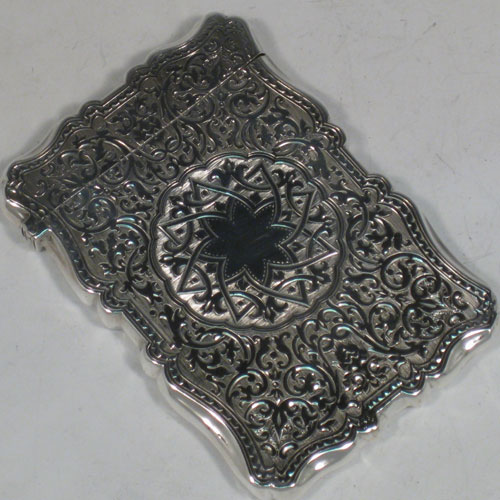 Antique Victorian sterling silver calling card case, having a shaped rectangular body with hand-engraved floral and geometrical decoration, and a side-hinged lid. Made by C. H. Cheshire of  Birmingham in 1876. The dimensions of this fine hand-made silver card case are length 10 cms (4 inches), width 7 cms (2.75 inches), and it weighs approx. 78g (2.5 troy ounces).