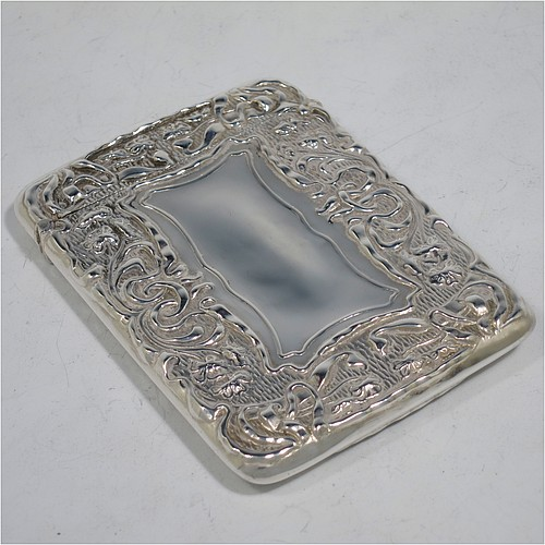 A very pretty Antique Edwardian Sterling Silver Art Nouveau card case, having a hand-chased rectangular body with floral and scroll decoration, a hanged lid, and two vacant cartouches on either side. Made by Cornelius Saunders and Frank Shepherd of Birmingham in 1905. The dimensions of this fine hand-made antique silver card case are length 9.5 cms (3.75 inches), width 7 cms (2.75 inches), and it weighs approx. 69g (2.2 troy ounces).