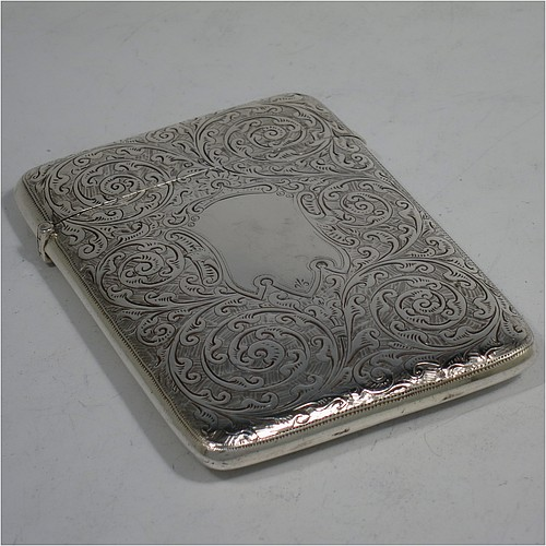 A very pretty Antique Victorian Sterling Silver calling card case, having a rectangular body with rounded shoulders, hand-engraved floral decoration, a vacant central cartouche on one side, and a side-hinged lid. Made by George Loveridge of Birmingham in 1898. The dimensions of this fine hand-made antique silver card case are length 10 cms (4 inches), width 7.5 cms (3 inches), and it weighs approx. 88g (2.8 troy ounces).