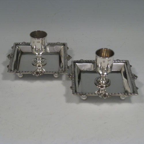 Antique Victorian sterling silver pair of small chambersticks with cast borders and sitting on four ball feet. Made by Edgar Finley and Hugh Taylor of London in 1891. Height 5 cms (2 inches), width 8 cms (3.25 inches) square. Weight approx. 6 troy ounces (186g).